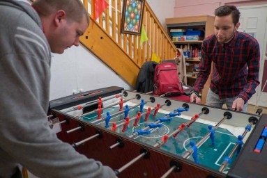 young men playing foosball
